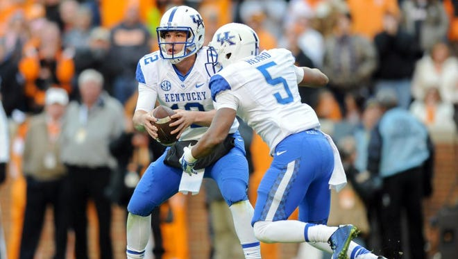 Nov 15, 2014; Knoxville, TN, USA; Kentucky Wildcats quarterback Reese Phillips (12) hands the ball off to running back Braylon Heard (5) during the first half against the Tennessee Volunteers at Neyland Stadium. Mandatory Credit: Randy Sartin-USA TODAY Sports