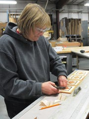 Dorry Gilmore does some assembly of an inlaid pattern for a boarder around a floor at Oshkosh Designs in Winneconne. All the employees are cross trained so that they may step in to get the job completed or fill in when needed.