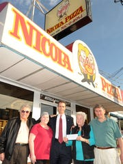 In this file photo, Nick Caggiano Sr., left,  Kelly Munyan, Alex Sydnor, Joan Caggiano and Nick Caggiano Jr. stand in front of Nicola Pizza in Rehoboth Beach after the Caggianos presented a check for $2,234 to Alex Sydnor of Beebe Hospital's Tunnell Cancer Center from monies raised at the restaurant.