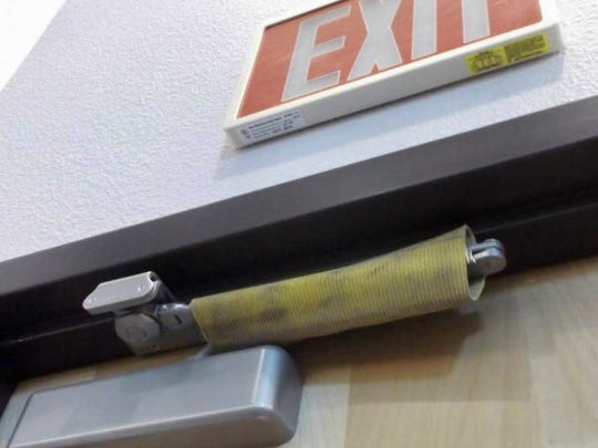 Fire hoses are wicked strong and when a section is slipped over the pneumatic door hinge, it  prevents the door from being opened in the event of an emergency.
