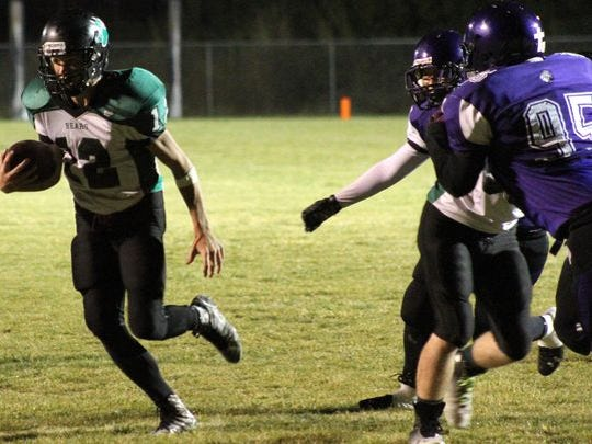 Alix Miller rushes past two Mescalero defenders Friday night at Chiefs Stadium. Mescalero defeated rival Cloudcroft 56-14.