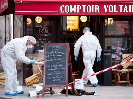 Police forensic experts work on the scene of one of the shootings that took place om Paris at the Cafe Comptoir Voltaire in Paris, Nov. 14, 2015.