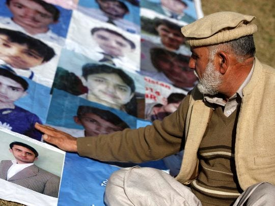 A man looks at portraits of victims, including his