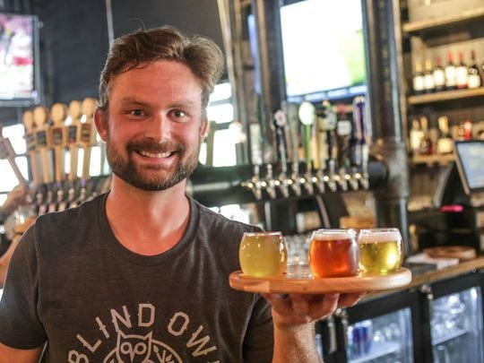 Drew Lee holds a beer flight at the Blind Owl Brewery, Kitchen and Bar soft opening in July 2015. The brewery is located at 5014 E. 62nd St.