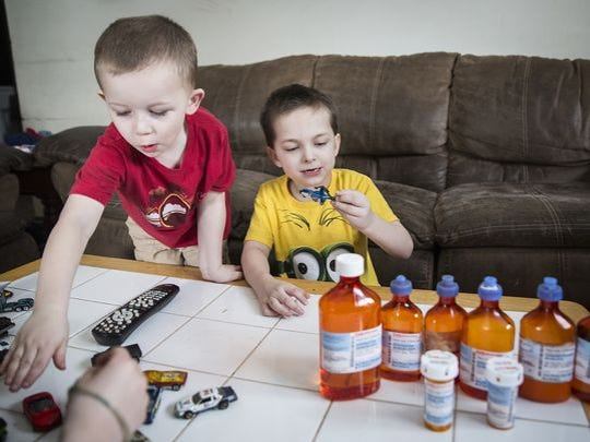 Tristan Stiffler (right) joins his cousin Nate Clifford and his older brother as they play with toys in the family's living room Tuesday.
