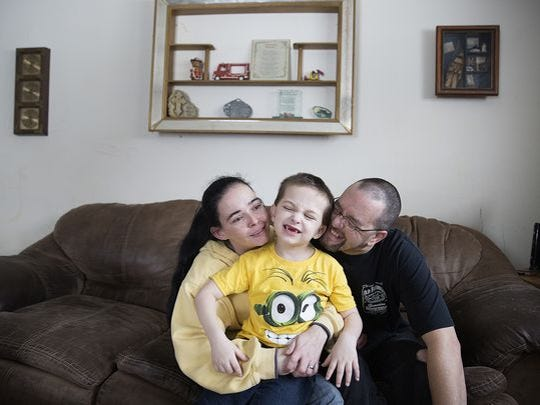 Tristan Stiffler, 6, spends time with his mother and father at their home in Hartford City Tuesday afternoon.