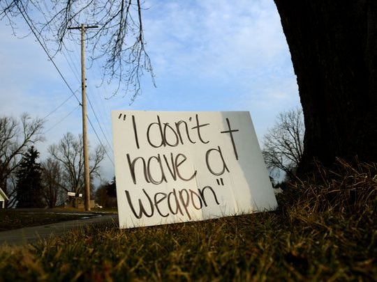 "A year after the death of Deven Guilford, a sign reads ""I don't have a weapon"" in front of a house by the sidewalk off Charlotte Street in Mulliken Friday, Feb. 19, 2016. Guilford was shot by Eaton County Sheriff Sgt. Jonathan Frost during a traffic stop. Frost was cleared of any criminal wrongdoing in the shooting."