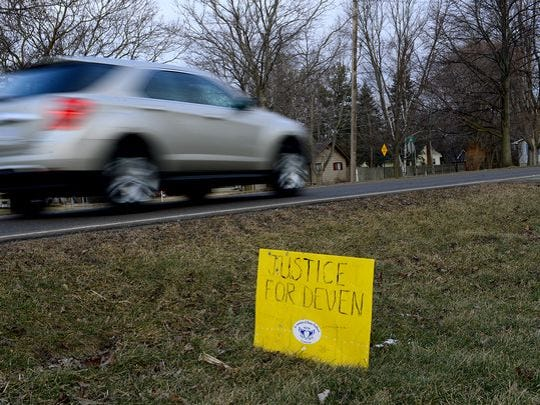 "A year after the death of Deven Guilford, a weathered sign reads ""Justice for Deven"" right off Charlotte Street in Mulliken Friday, Feb. 19, 2016. Guilford was shot by Eaton County Sheriff Sgt. Jonathan Frost during a traffic stop. Frost was cleared of any criminal wrongdoing in the shooting."