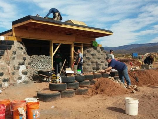 Volunteers work to construct Foxhole Homes' first earthship.