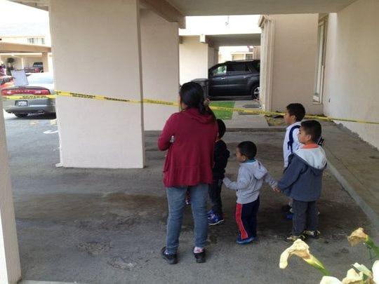 Una mujer con varios niños esperan a que la policía los pueda dejar regresar a su casa.
