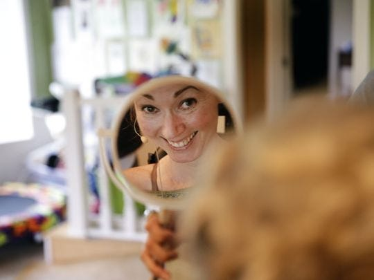 Jenni Berebitsky smiles in the mirror after having her makeup done by cousin Leslie Dinneen before her party.
