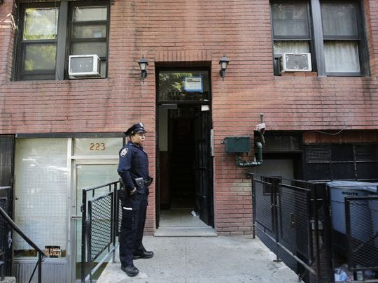 A New York Police Department officer stands outside an apartment building where Kiersten Rickenbach Cerveny had a fatal overdose in October 2015.
