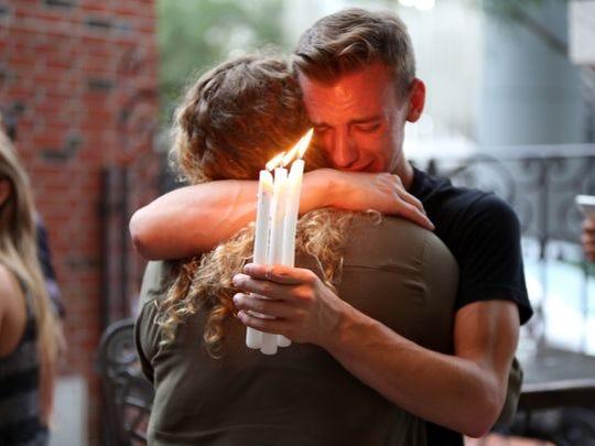 Brett Morian, from Daytona Beach, hugs an attendee