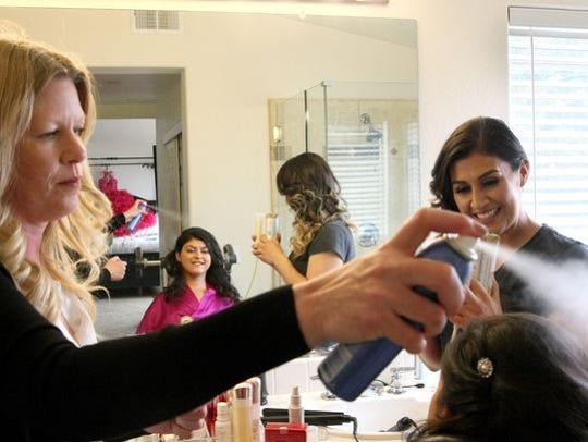 La estilista Leah Santibanez rocía espray en el cabello