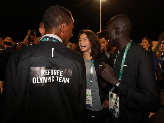 Yusra Mardini, center, of Syria with fellow team members