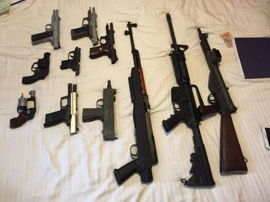 A federal agent alleged that officials found 11 firearms at Wayne Wallace's home, including a fully automatic rifle, seen on the far right, that was reported stolen in Georgia in April 2015.