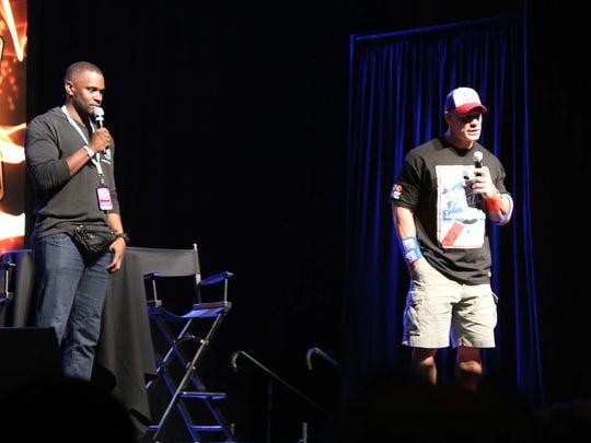 Professional wrestler John Cena, right, talks to one