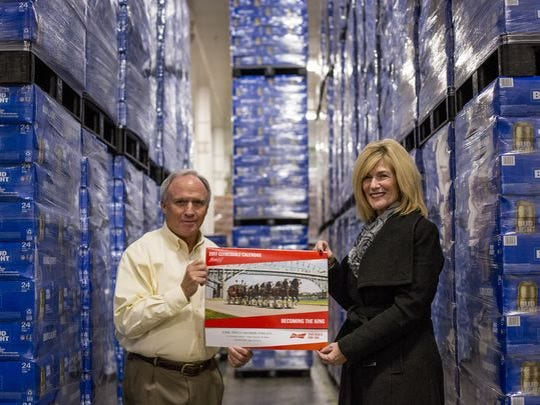 Rick Dionne, vice president, and Port Huron Mayor Pauline Repp hold up the 2017 Budweiser calendar Thursday, Dec. 8, 2016, at Earl Smith Distributing in Port Huron.