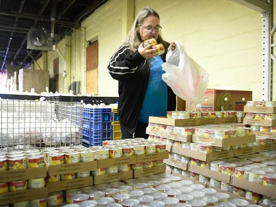 In this file picture, a volunteer loads food supplies at the Tri State Food Bank.