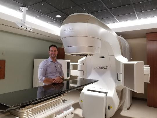 Peter Heiberger, M.S., medical physicist, stands behind the newly installed TrueBeam linear accelerator at Aurora Cancer Care Clinic in Two Rivers.