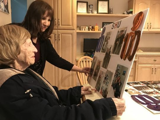 Fran La Sala looks at a poster with photos commemorating her time working at Seton Hall University, along with her daughter, Joann Candido.