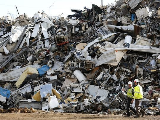 John Eide and Mark Lasky walk past a pile of scrap