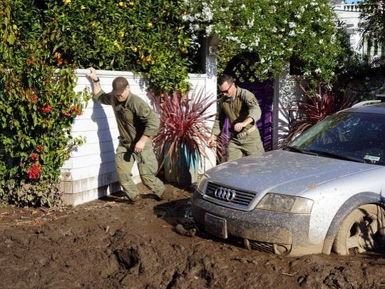 Deputies with the Santa Barbara County Sheriff's Office clamber though mud outside a home Jan. 14, 2018, as they search for people who refused to evacuate during the mandatory evacuation of the town following deadly mudslides. The slides killed at least 20 people, and destroyed or damaged hundreds of homes and vehicles.