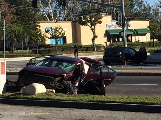A crashed Nissan Maxima sits in the intersection of