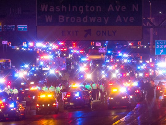 Demonstrators are surrounded and arrested by police after blocking a portion of Interstate 94, shutting down the northbound lanes, Monday, Nov. 16, 2015, in Minneapolis.