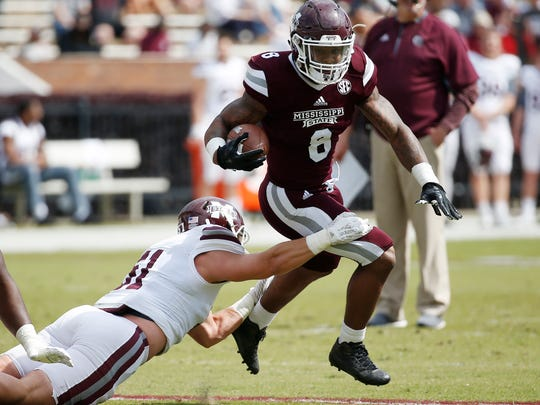 Maroon running back Kylin Hill (8) runs through a tackle attempt by White linebacker R.J. Jennings (51) during the first half of Mississippi State's spring NCAA college football game Saturday, April 21, 2018, in Starkville, Miss. Maroon won 28-10. (AP Photo/Rogelio V. Solis)