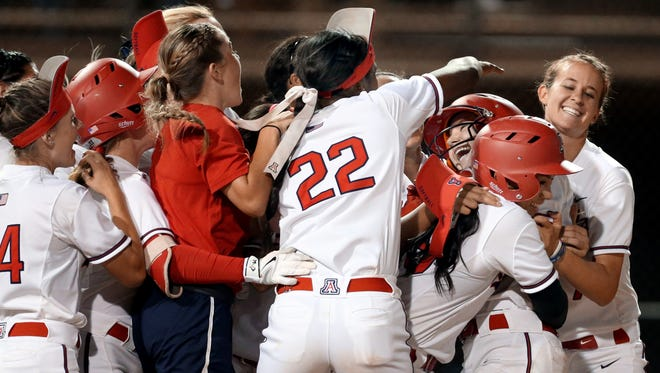 Arizona's Jessie Harper (19), third from right, gets swarmed by her teammates after her bases loaded single in the bottom of the seventh drove in the winning run in 3-2 victory over Baylor in their NCAA Super Regional playoff game at Hillenbrand Stadium, Friday, May 26, 2017, Tucson, Ariz.  Kelly Presnell / Arizona Daily Star