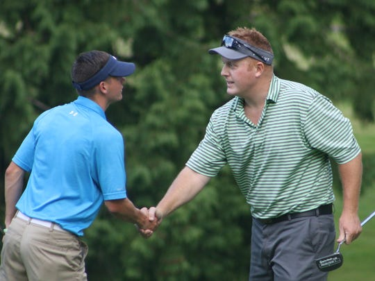 Tres Kirkebo (right) shakes hands with runner-up Zach Lund after winning the Kitsap Amateur golf tournament title Sunday at Kitsap Golf & Country Club.