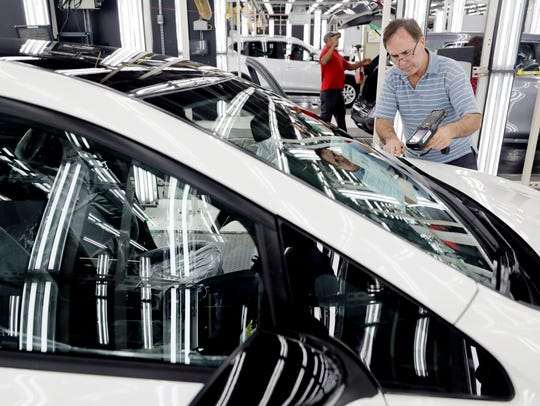 An employee at Nissan's Smyrna plant scans a completed