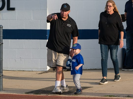Stephen Decatur football coach Bob Knox walks with his grandson Eli Tadli, 3, on the field before a game against Kent Island on Friday, Sept. 22, 2017.