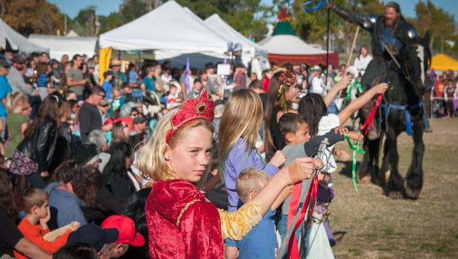 Attendees to a joust hold up ribbons for riders to collect during last year's 44th annual Renaissance ArtsFaire at Young Park.