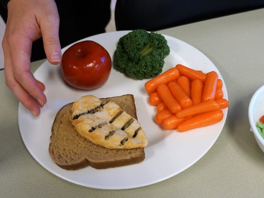 Students with NMSU's Dietetic Internship Program use rubber food replicas to create what a nutritonally balanced dinner plate should look like. The program was recently accredited by the Accreditation Council for Education in Nutrition and Dietetics.