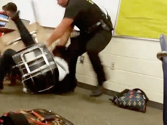In this Monday, Oct, 26, 2015 photo made from video taken by a Spring Valley High School student, Senior Deputy Ben Fields tries to forcibly remove a student who refused to leave her high school math class, in Columbia S.C. The Justice Department opened a civil rights investigation Tuesday after Fields flipped the student backward in her desk and tossed her across the floor. (AP Photo)