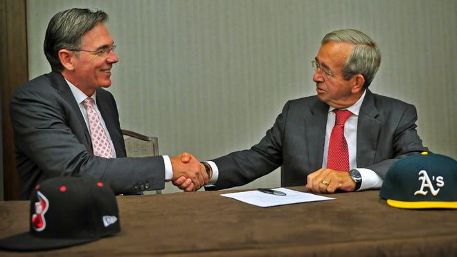 A's General Manager Billy Beane, left, shakes hands with Sounds owner Frank Ward after both signing the agreement during a press conference at Omni Hotel.