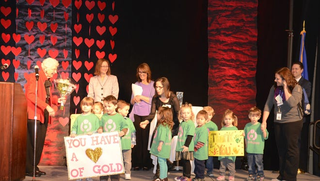 Children from the Encompass Early Education and Care Inc. Carol B. Bush Center in Green Bay surprised Carol Bush, left, on stage after she received the Morgan Stanley Heart of Gold Lifetime Achievement Award .
