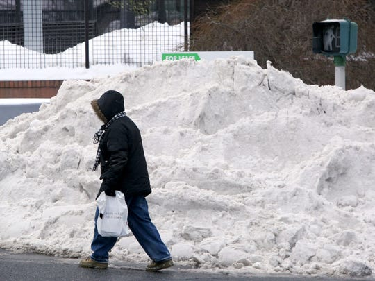 A pedestrian walks around a pile of snow on the corner of Quarropas and Grand streets in downtown White Plains the day on Wednesday.