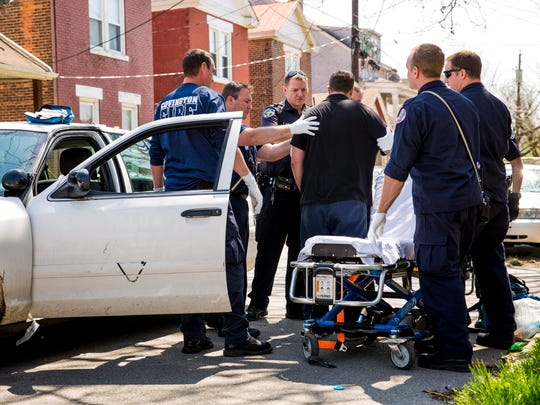 Paramedics of the Covington Fire Department help a man, who overdosed, after they administered Narcan to restore his breathing Thursday, April 13, 2017 in Covington, Kentucky.