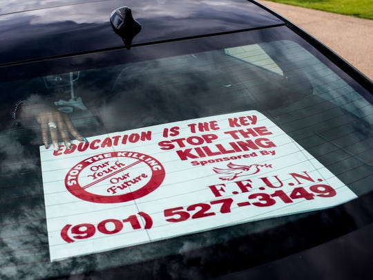 """A Stop the Killing sign is put in the back of a car before the start of the """"Ride of Tears"""" event that started at the Liberty Bowl and moved throughout the city June 21, 2017."""