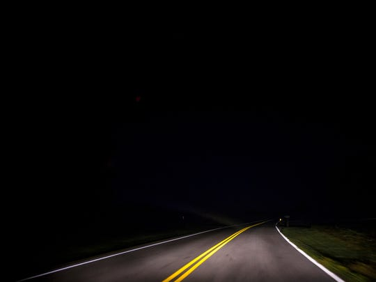 Headlights illuminate a road in Christian County, Kentucky