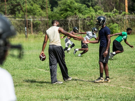 August 8, 2017 - Terrance Ayers, left, slaps hands with starting quarterback Josh Marion during practice at Mitchell High School. ÒItÕs my dad, he adopted me my freshmen year of high school,Ó Ayers said about head coach Nathan Cole who is one of the reasons Ayers wanted to return to Mitchell and help coach.The Mitchell Tigers football team practices for the upcoming 2017 season.
