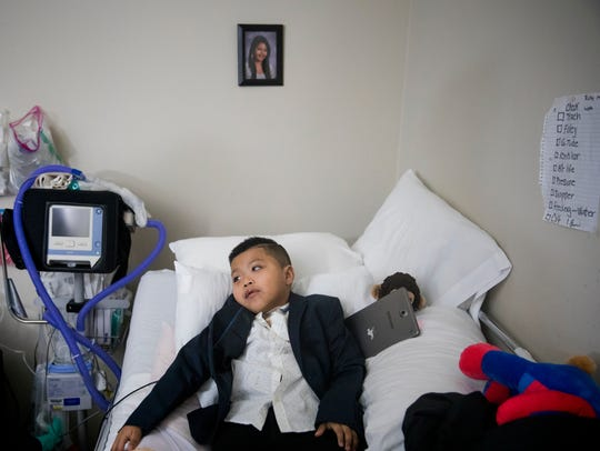 Ricky Solis, 6, lays in bed after his mom and nurse