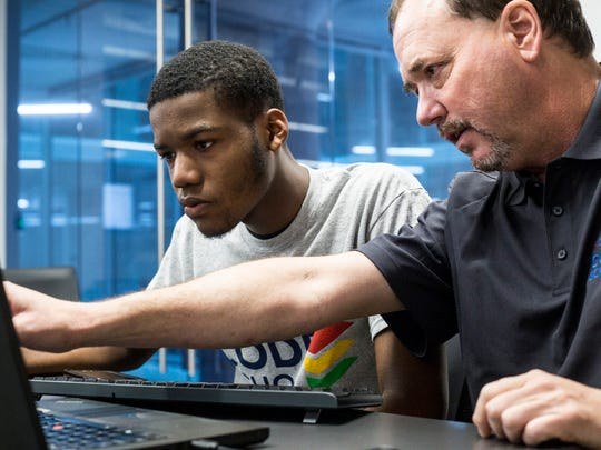 Teacher Kevin Yancy, right, helps Mareco Nabors during Code Crew's new Code School on July 20, 2018, at Crosstown Concourse.