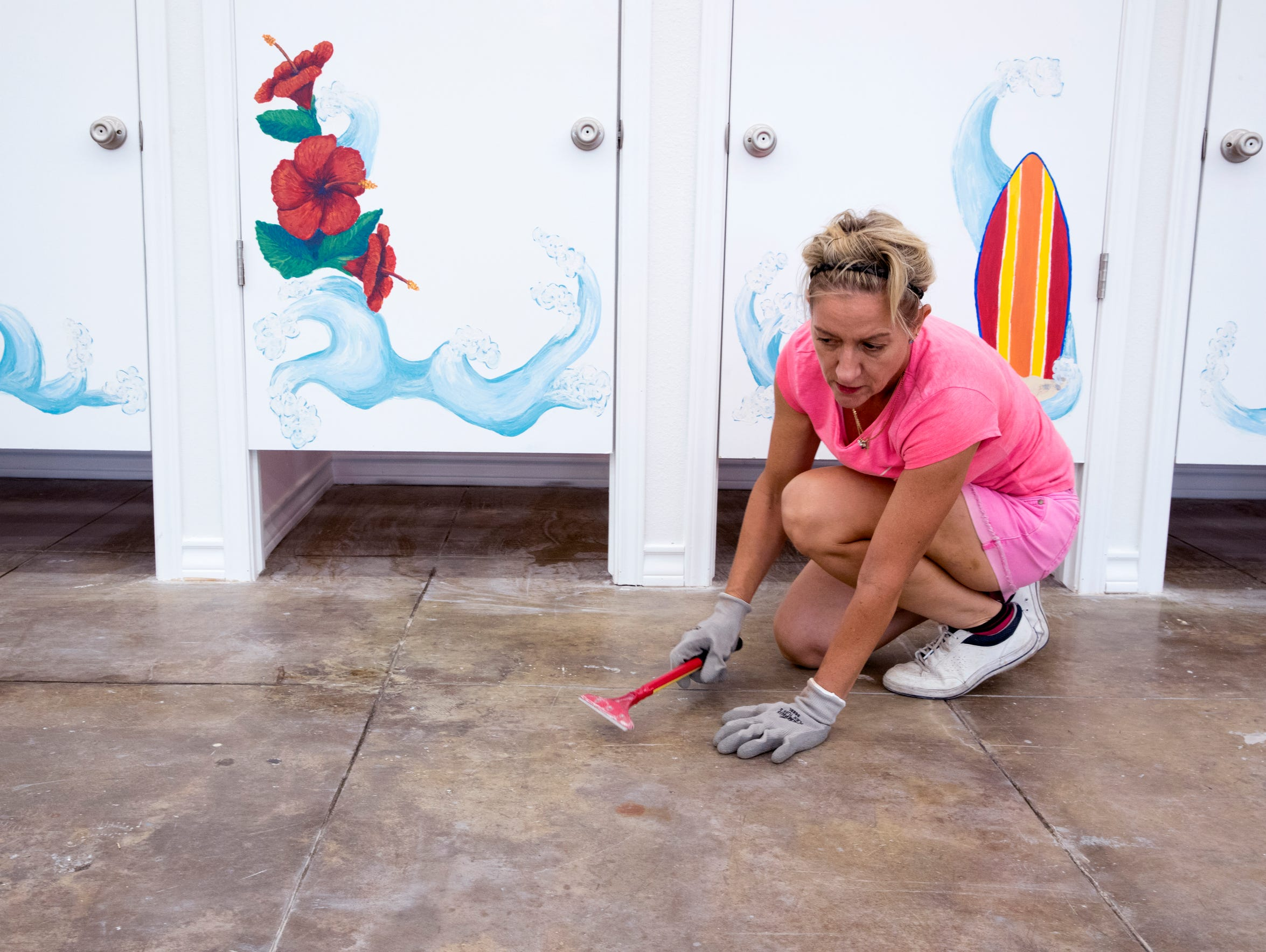 Pam Luebke works to clean the floors at Island Sports,
