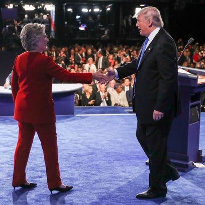 Republican presidential nominee Donald Trump speaks as Democratic presidential nominee Hillary Clinton listens during the presidential debate at Hofstra University.