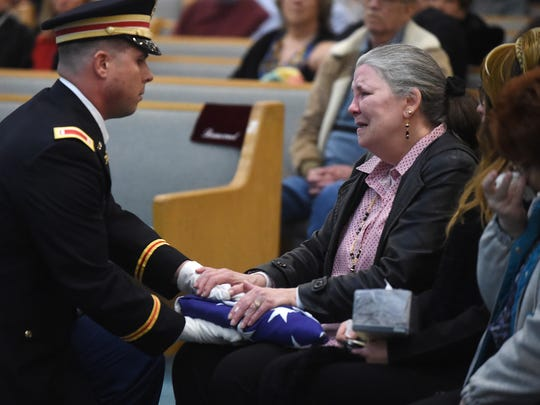 A member of the U.S. Army Honor Guard presents a flag to the family of Perry Boore on Saturday during his memorial service at Twin Lakes Baptist Church. Boore, a Korean War veteran, received Military Honors.