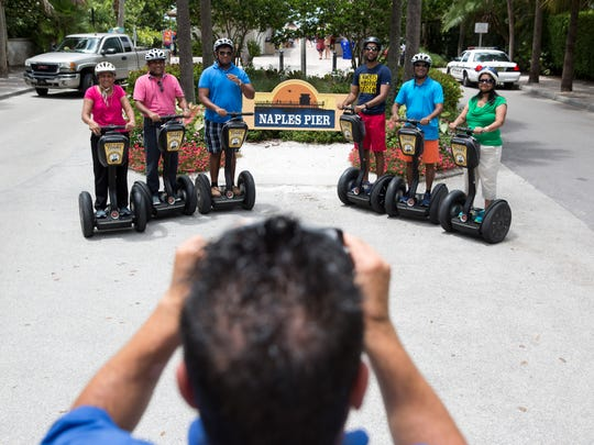 Dominick Dimolfetta, a tour guide with Segway Tours of Naples, takes a photo of the Patel family, visiting from Ocala, Fla., during a stop at the Naples Pier on Friday, Aug. 12, 2016.